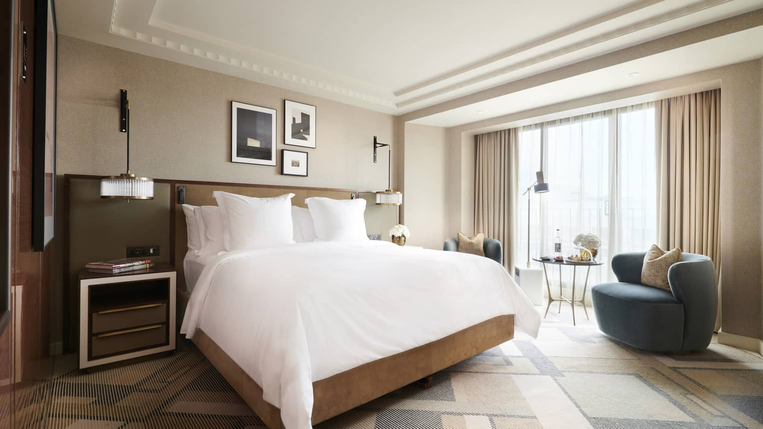 Floor to ceiling windows let natural light into the Deluxe King Room, furnished with a modern king bed, a modern egg-shaped blue chair and side table