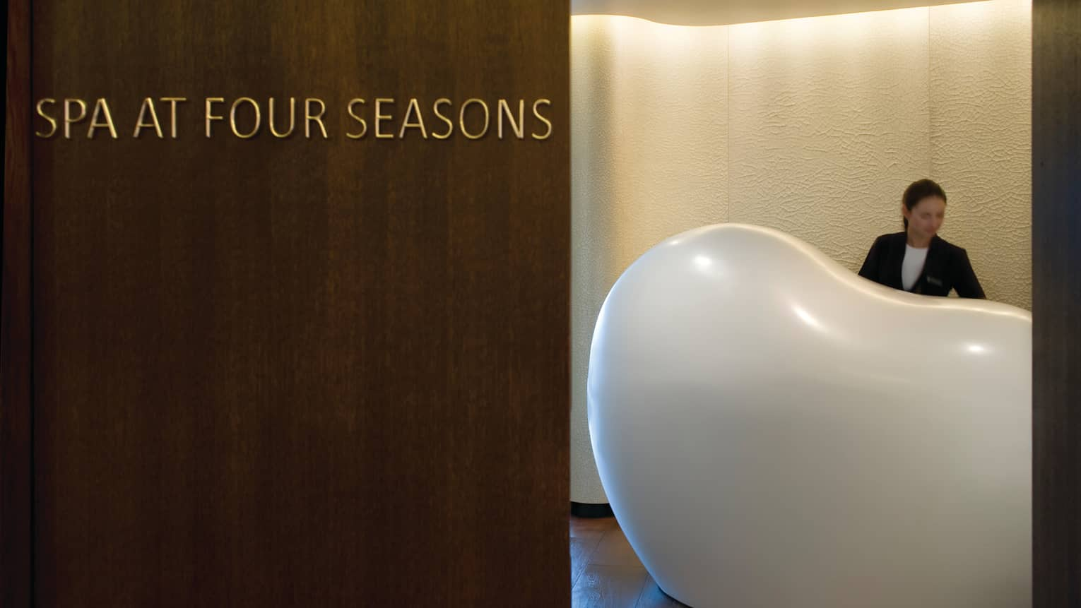 Hotel staff behind white, modern, bean-shaped desk, Spa at Four Seasons sign