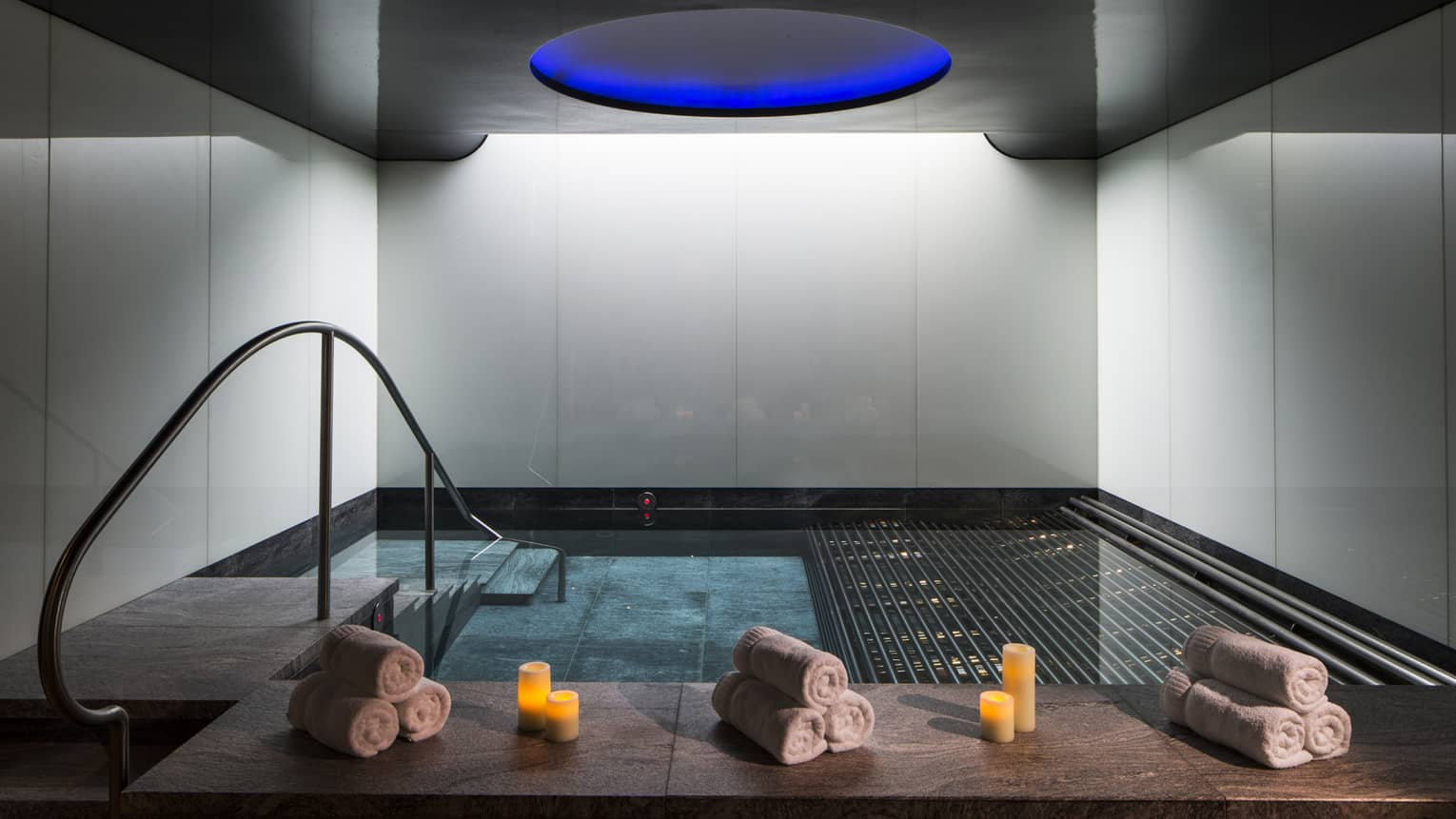 Rolled white towels, candles on spa vitality pool ledge under blue dome ceiling