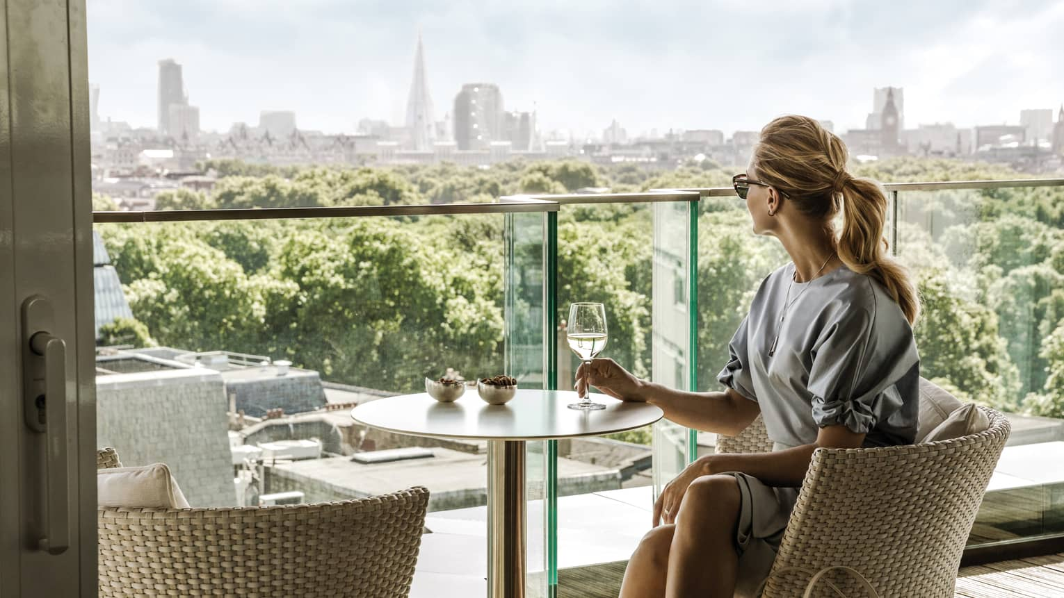 Woman sits at patio table with glass of wine, looks over glass balcony to trees, London skyline