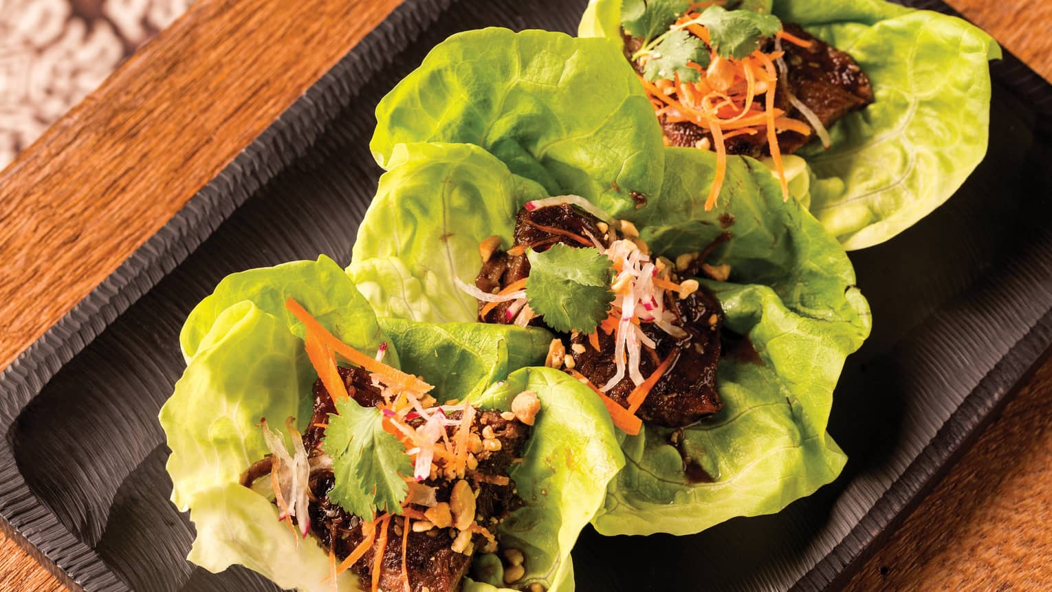 Three Kalbi Rib Lettuce Wraps with braised short ribs on platter