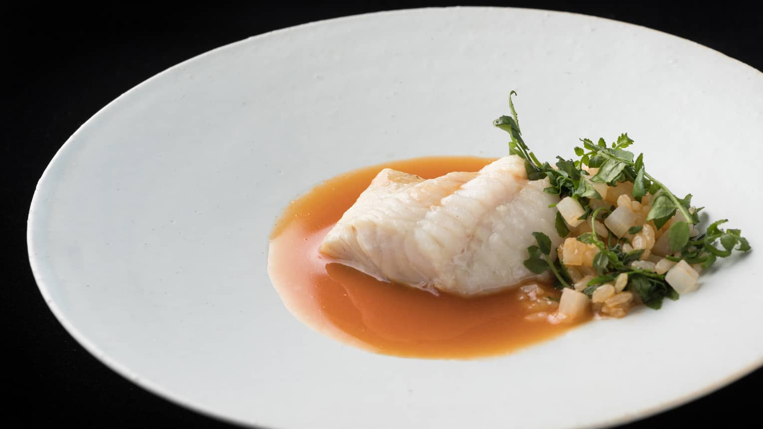 Motif Restaurant dish with white fish fillet in sauce, chopped vegetables, grains in sauce