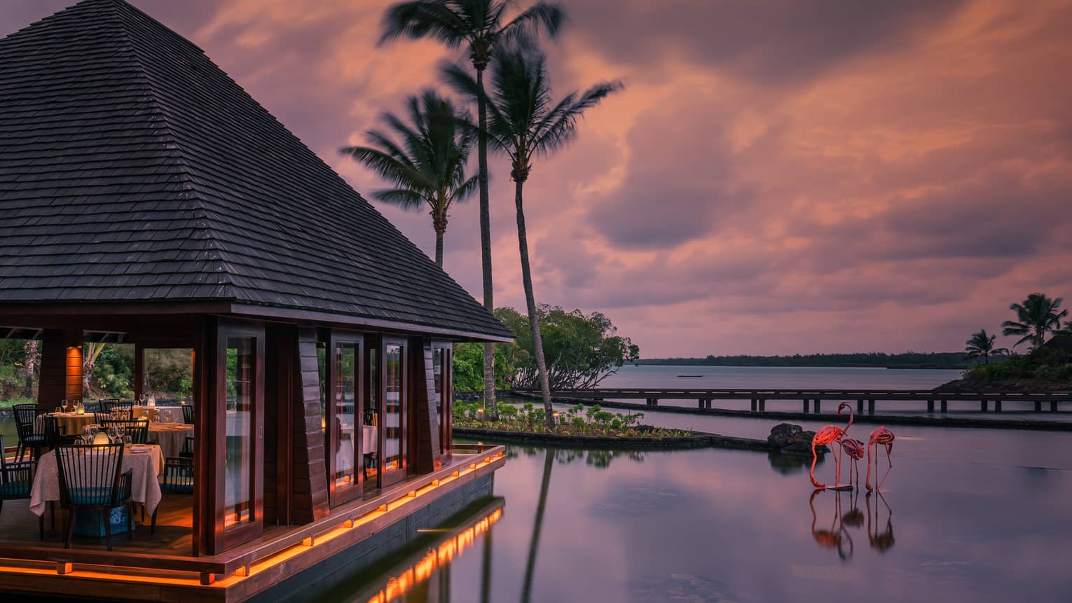 Beau Champ restaurant pavilion at sunset, two pink flamingo sculptures in water