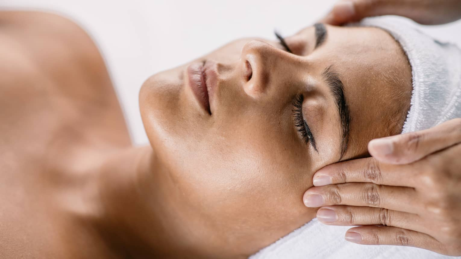 Hands massage woman's temples as she closes her eyes, spa towel around hair