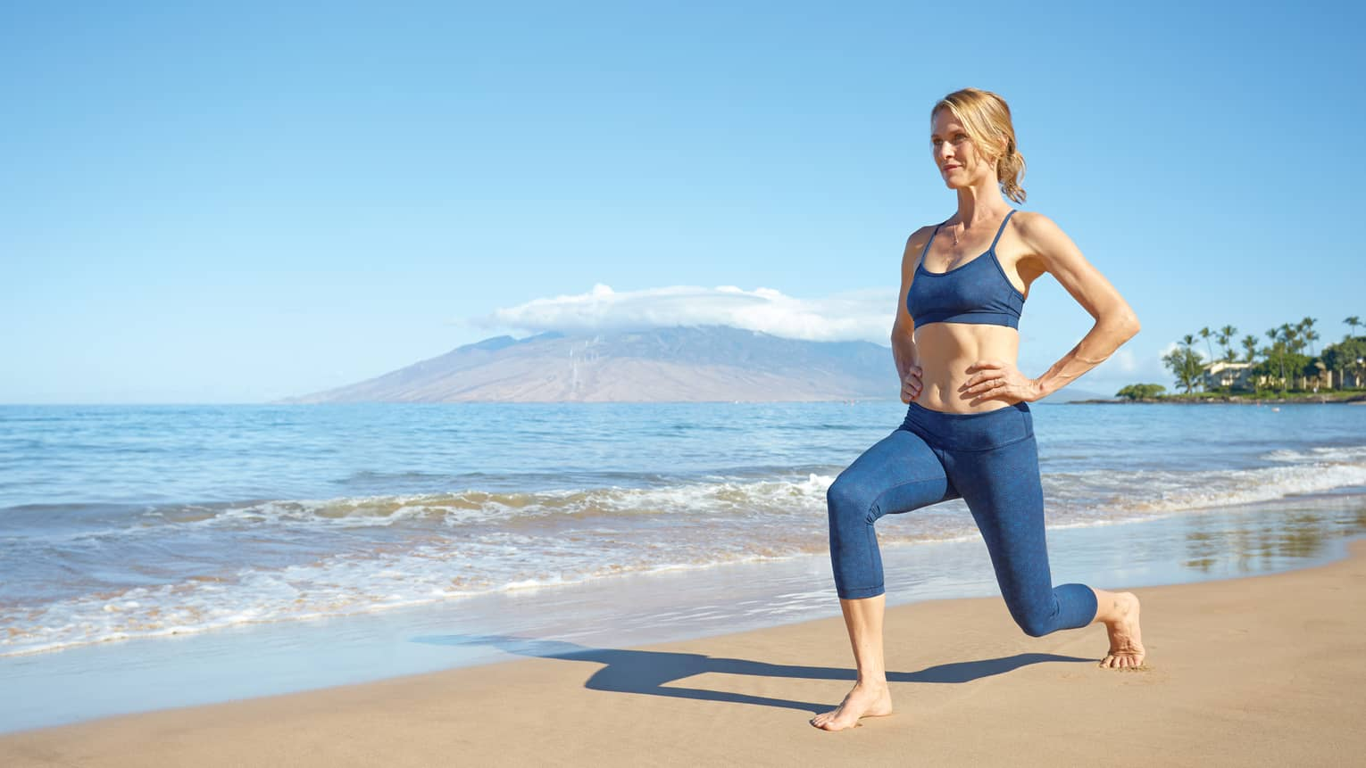 Woman in workout gear does yoga pose on beach by shore