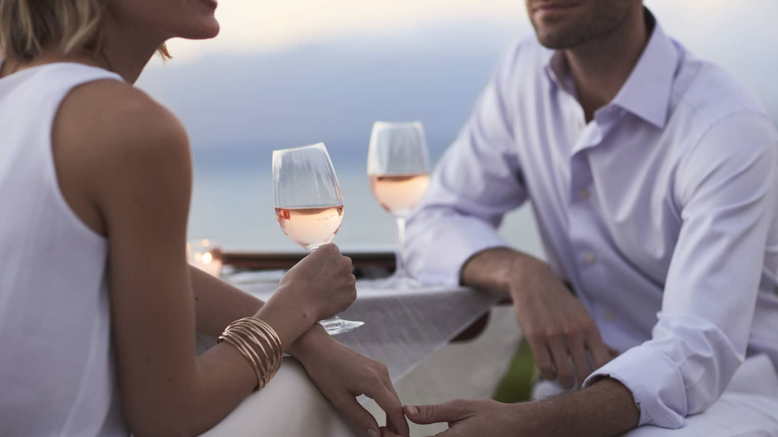Close-up of woman and man in white, sitting and holding glasses of rose wine at dusk