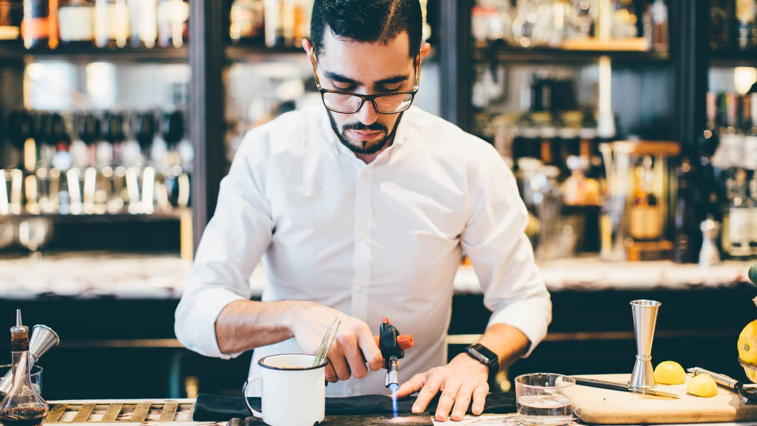 Bartender at Fifty Mils bar with small torch, blue flame over platter beside coffee cup