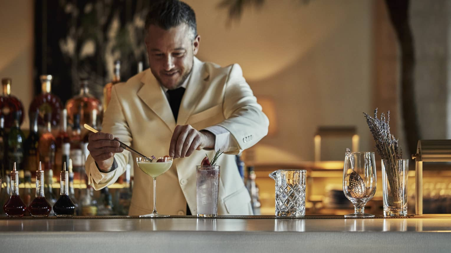 Surf Club Ballroom. Mixologist in a white suit stands behind the bar, garnishing signature Mangareva cocktail