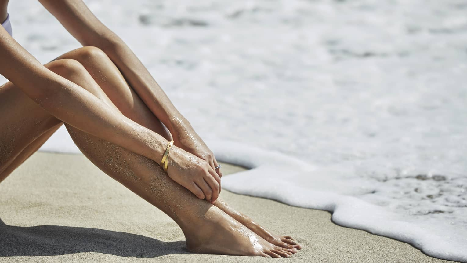 Close-up of woman's arms resting on bare legs as she sits on sand beach by ocean