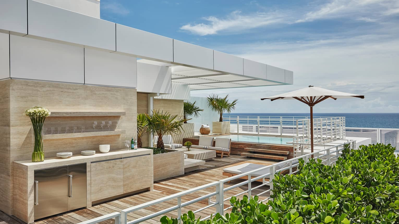 Marble outdoor bar and kitchenette with glasses, flowers, white sofas on modern rooftop patio with ocean views