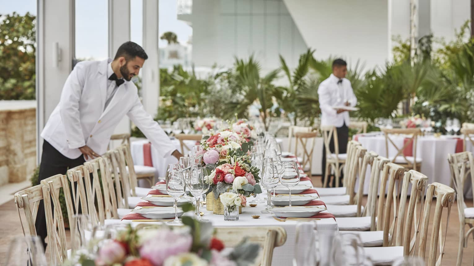 Hotel staff wearing white suit jackets set long wedding dining table with flowers