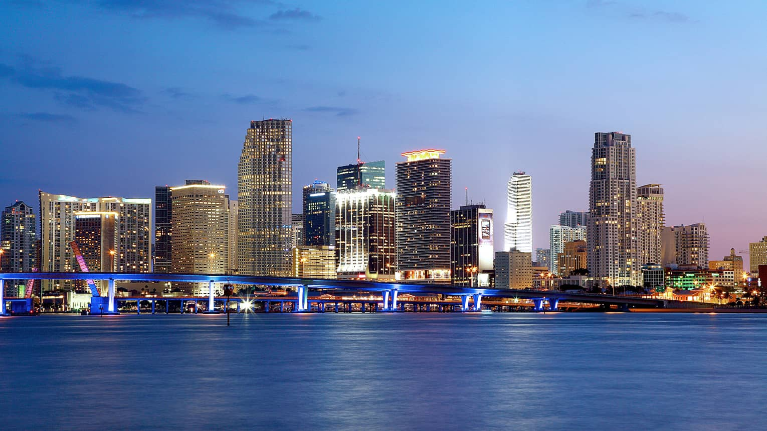 Miami highrise buildings with lights along water at night