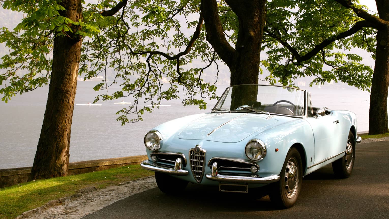 Light blue luxury Giulietta Spider convertible car parked on road by trees, water