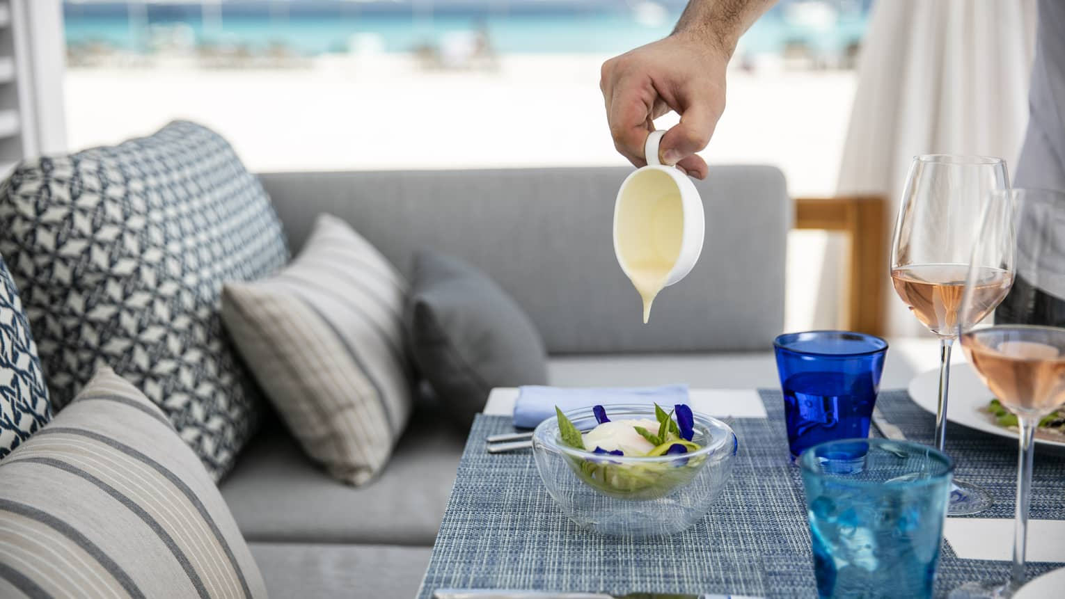 A person pouring some kind of glaze over a dish on a tastefully set table overlooking the ocean in Four Seasons Maldives - Landaa