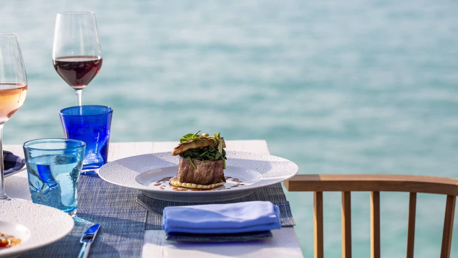 A table with a glass of red wine and a beef dish overlooking the ocean at Four Seasons Maldives - Landa