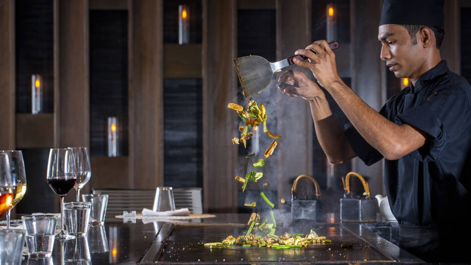 A four seasons dining staff working on a towering dish made of vegetables at the bar