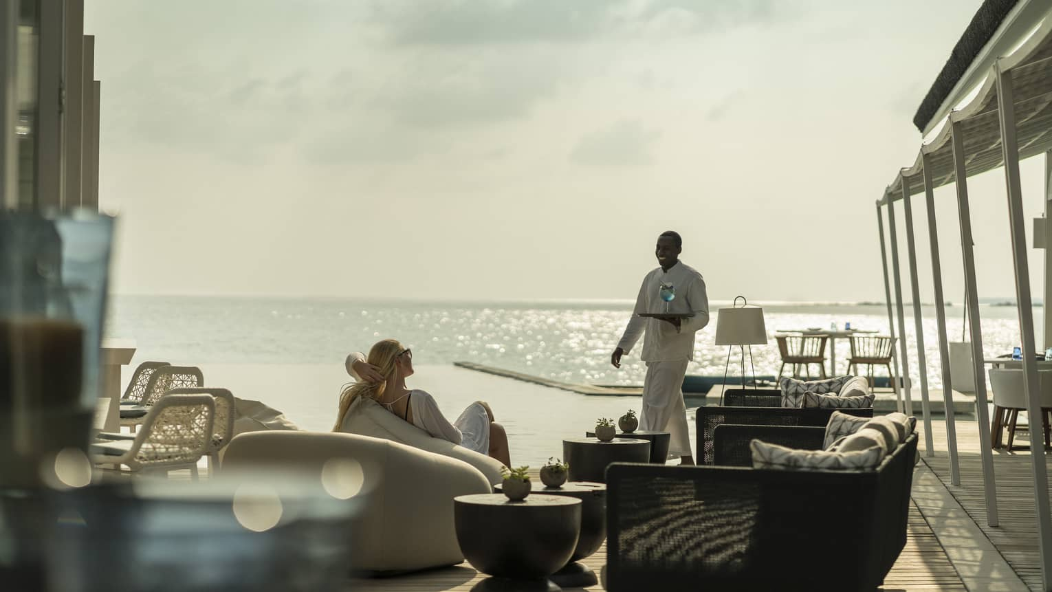 A guest receives a cocktail while relaxing outside at the Blu Beach Club