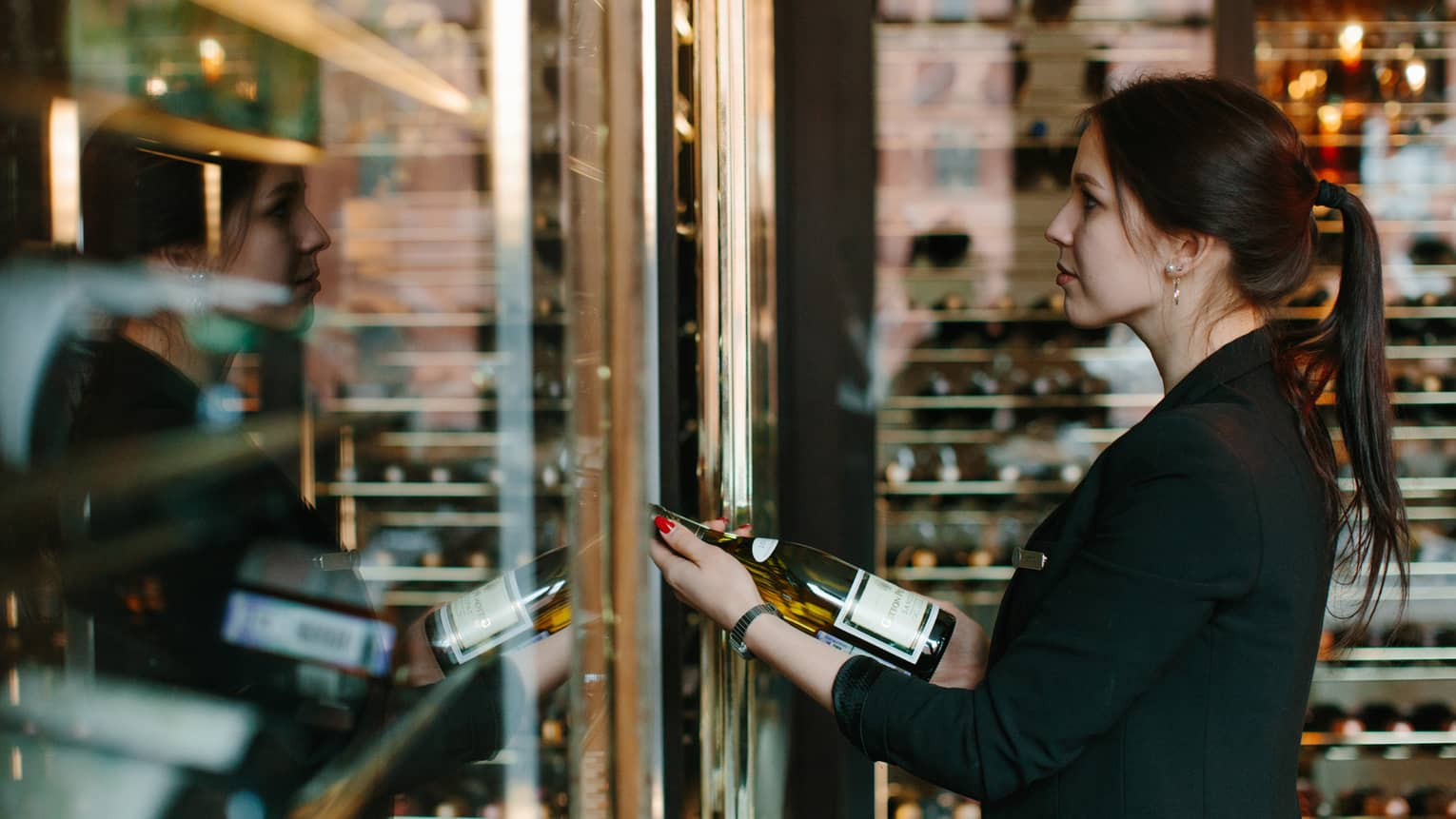 Wine sommelier examines bottle at glass cellar