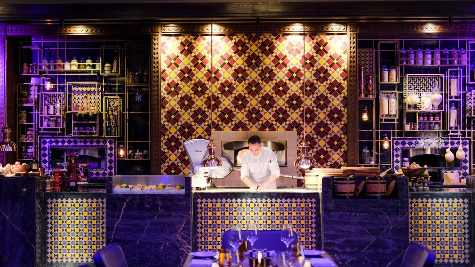Chef presses dough on counter with colourful tiles, lights, in front of dining table