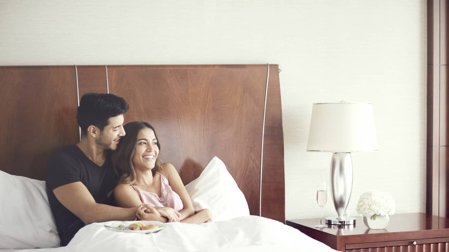 Couple cuddles in bed in modern hotel room