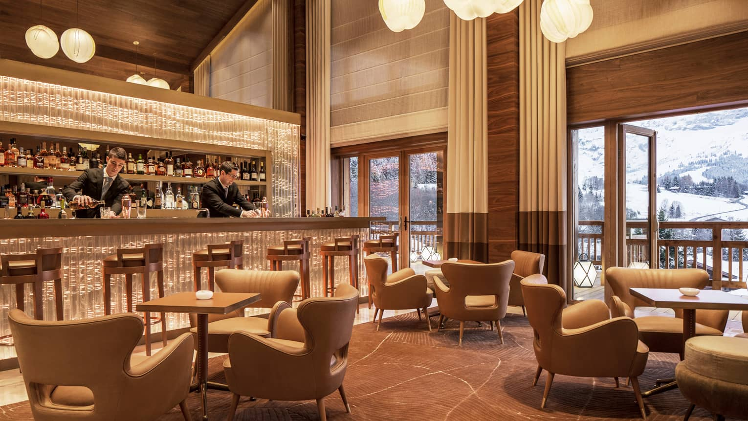 Bartenders mix drinks at Le 1920 bar by midcentury-style lounge chairs, tables, under soaring ceilings