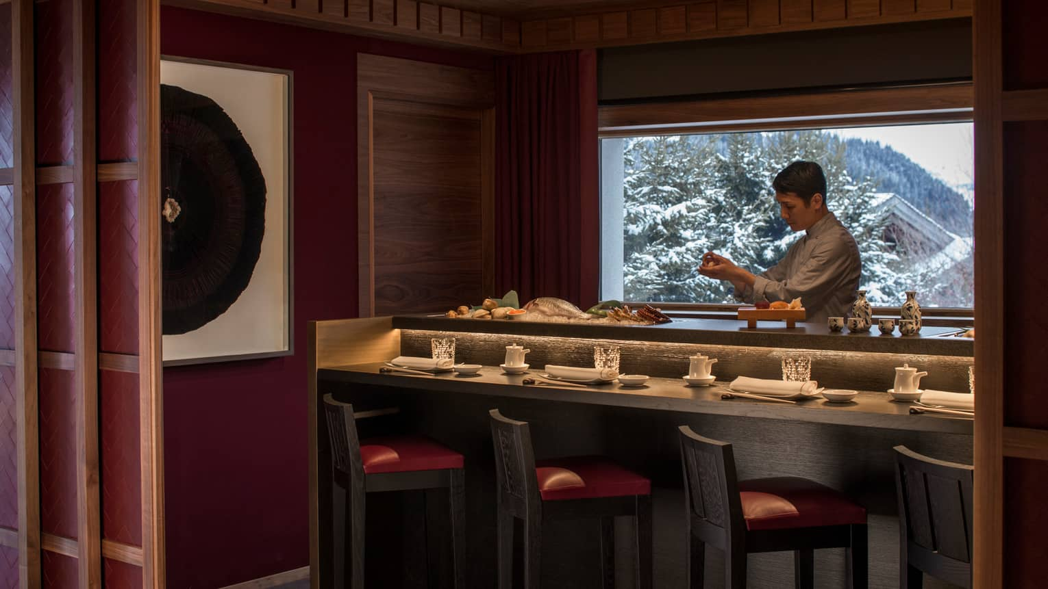 Kaito sushi chef at small bar with fresh whole fish, seafood, window with winter mountain views