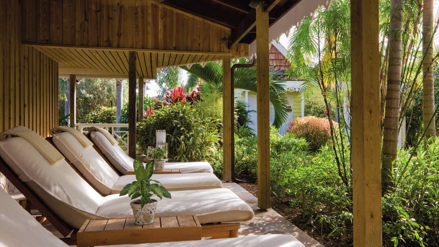 Plush white lounge chairs under wood patio facing tropical garden