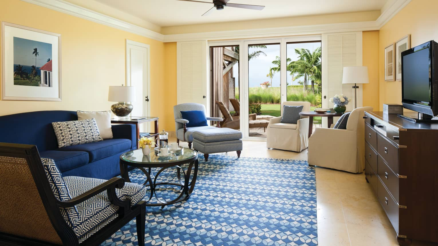 Ocean Suite blue sofa, patterned carpet, armchairs by glass balcony doors