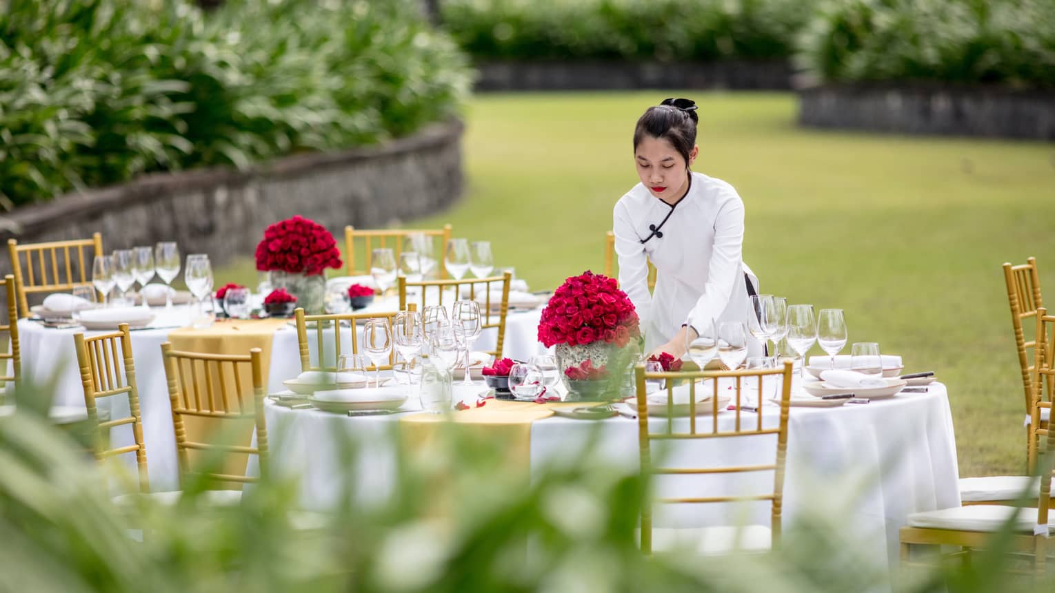 A staff member sets a table out in the lawn with red flowers for a wedding