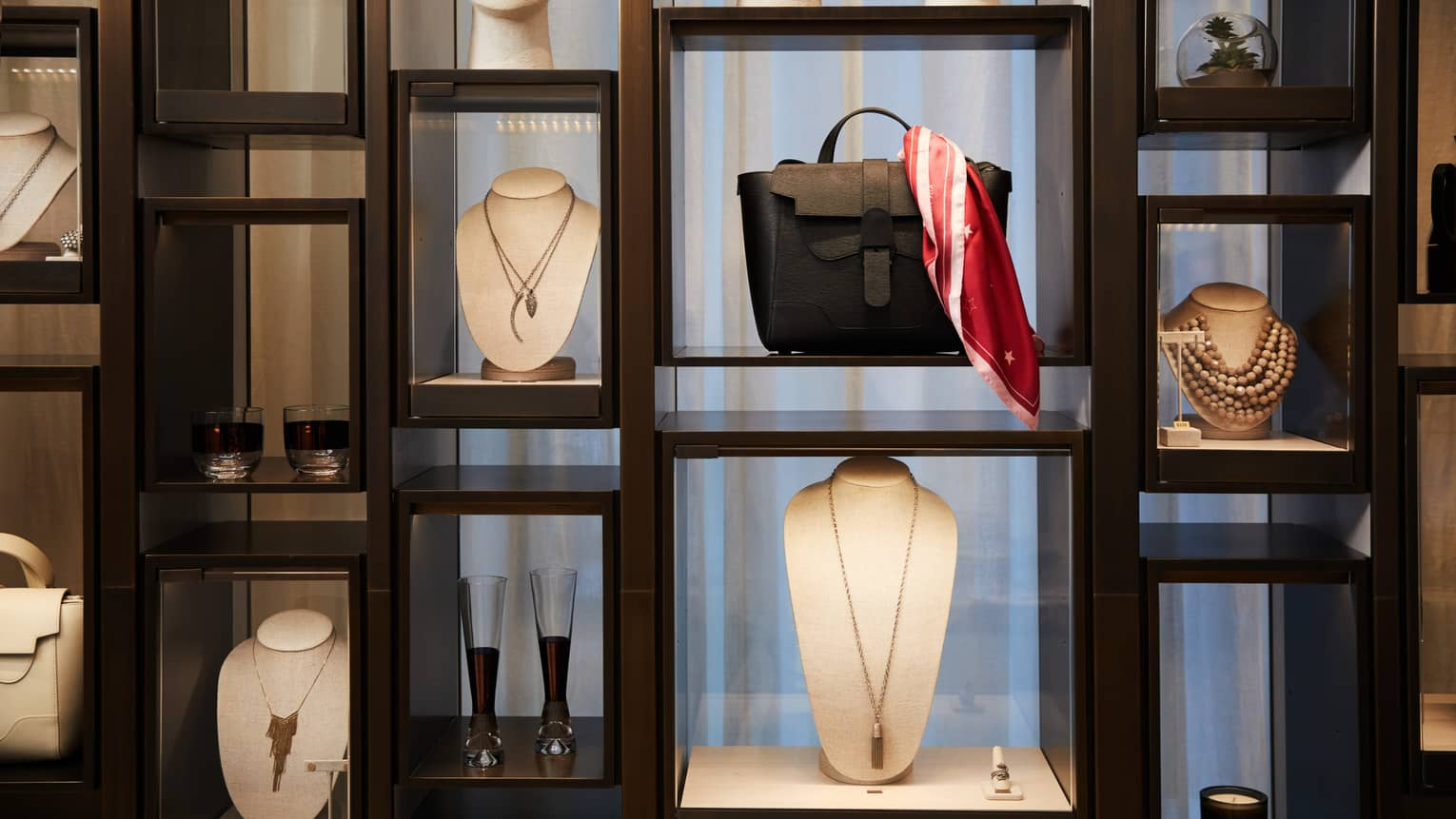 Boutique retail store shelf with designer necklaces, handbag, cocktail glasses
