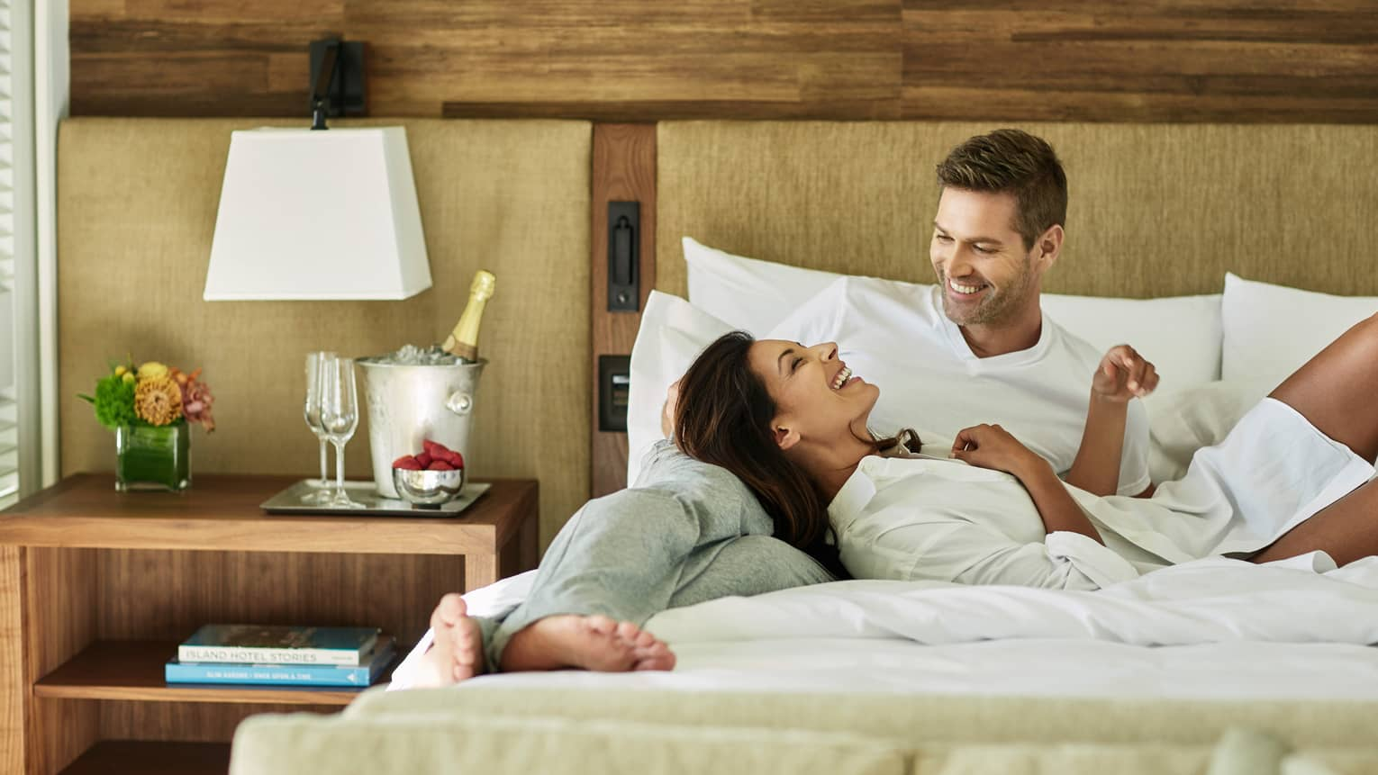 Woman and man laugh, lounge on hotel room bed by Champagne, rustic wood wall