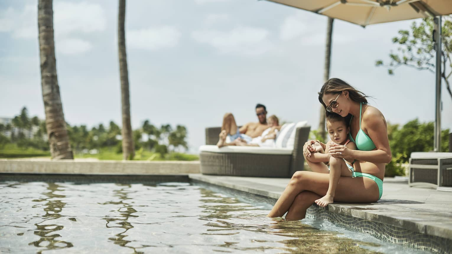 Mom in swimsuit sits on pool edge, cuddles young child, dad and daughter on patio chair