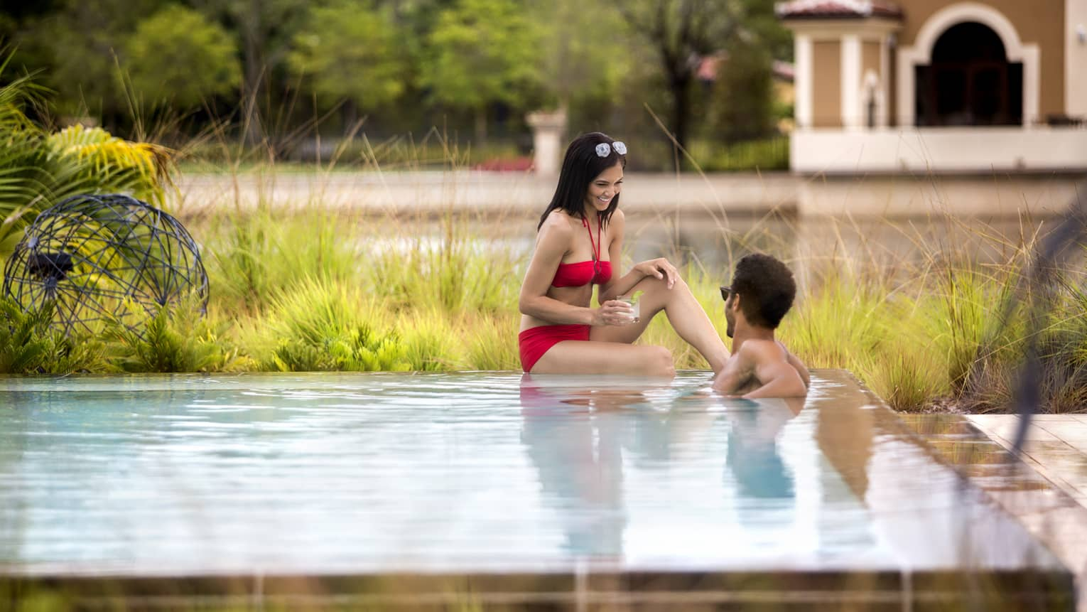Woman wearing red bikini sits on edge of Adult Pool, made wades in water