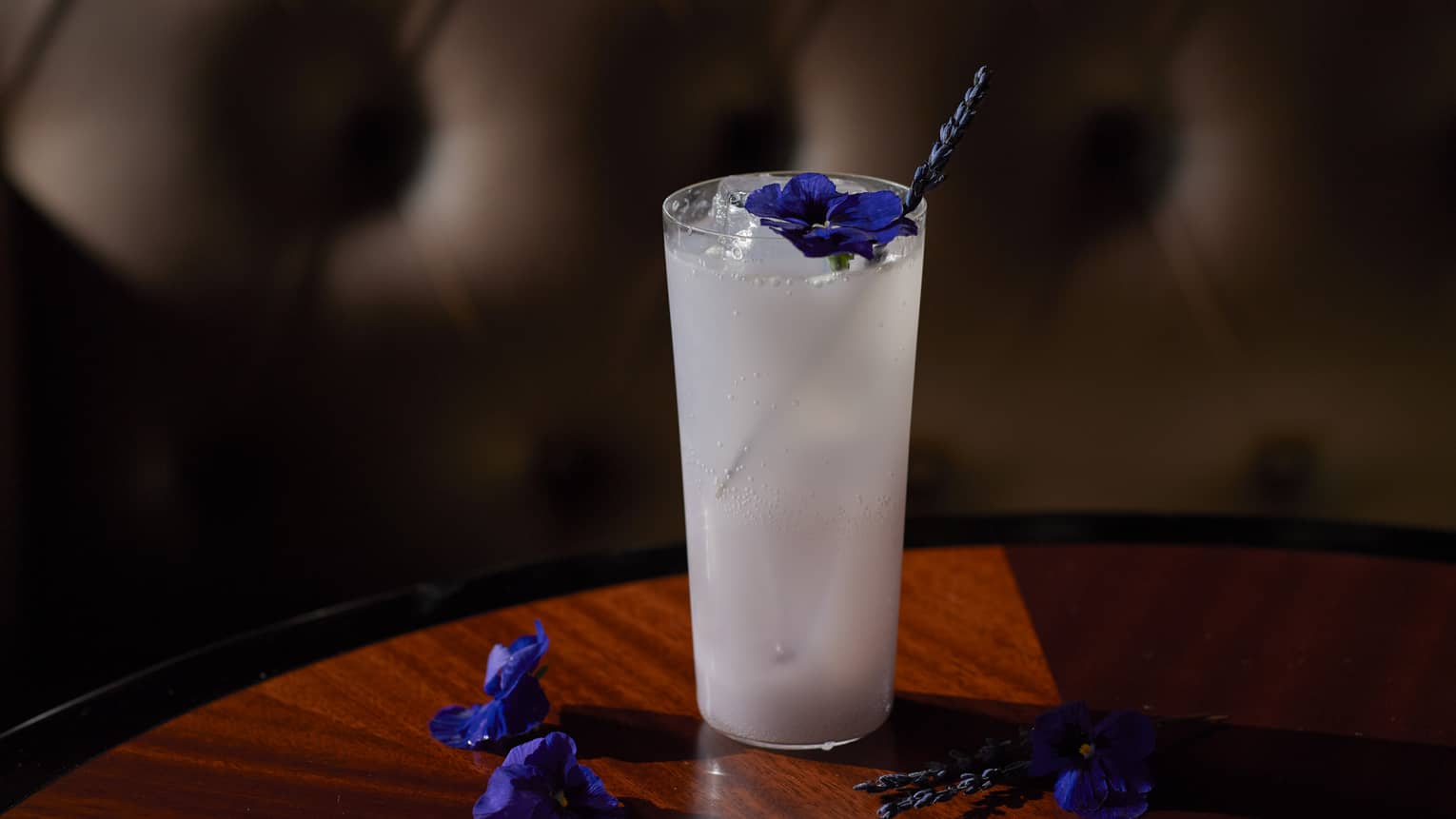 Close-up shot of milky white cocktail on the rocks, garnished with lavender and morning glory flowers atop wooden table