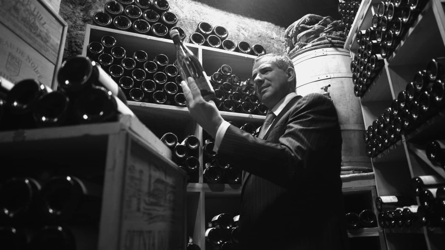 Black and white photo of wine sommelier selecting bottle from cellar