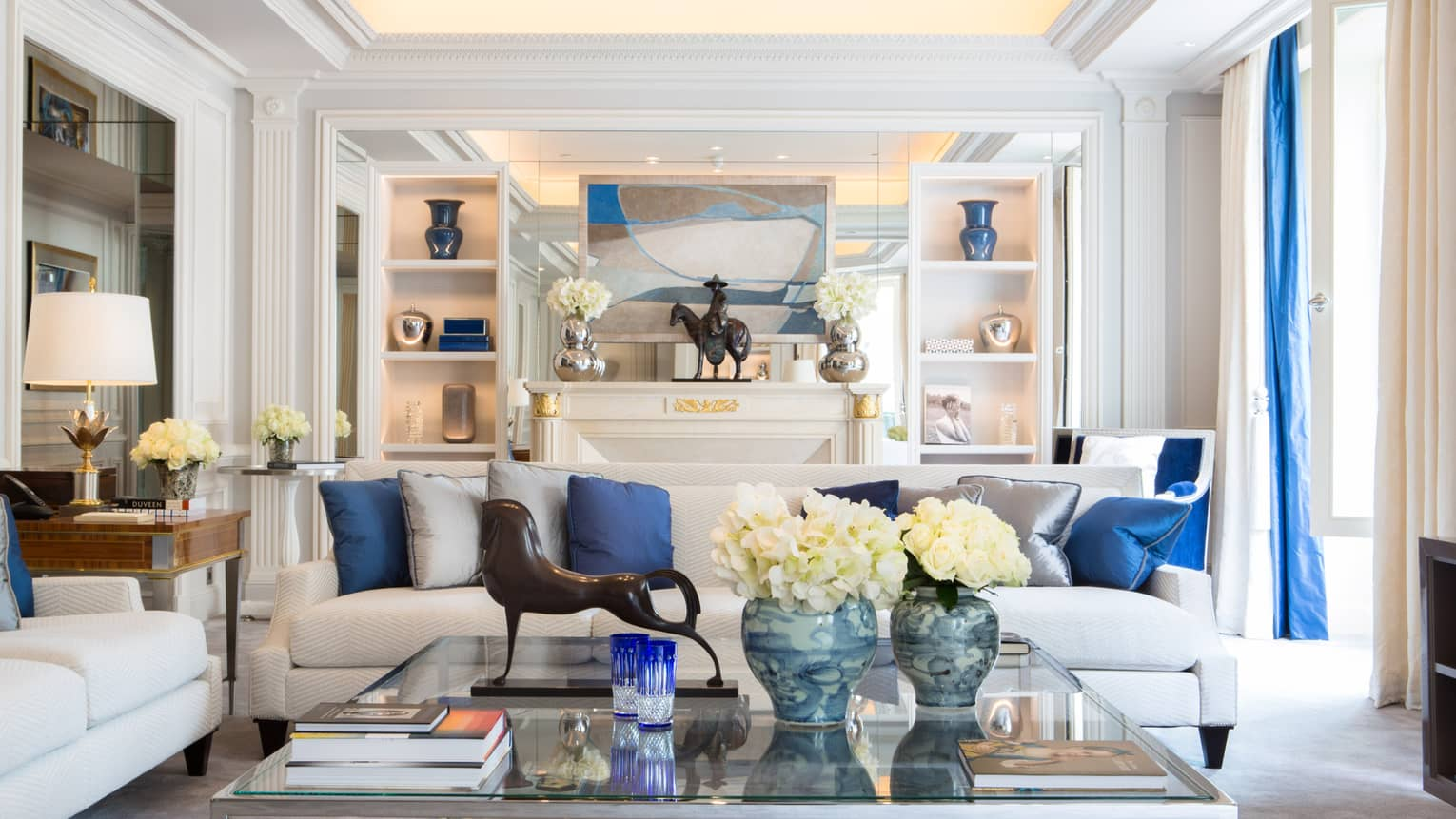 Presidential Suite long white sofa with blue pillows, glass coffee table with modern horse statue, flowers