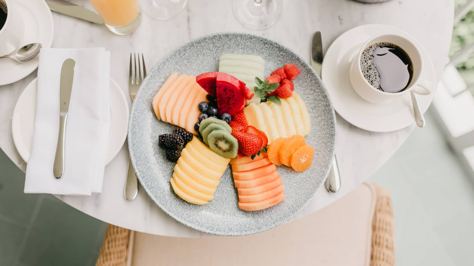 Plate of assorted sliced fruits and whole berries, place setting, coffee