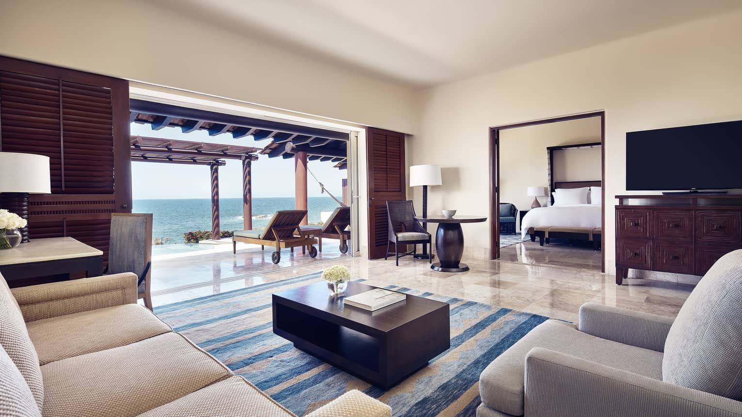 Oceanfront Suite spacious living room, sofas by bedroom door and open wall to patio