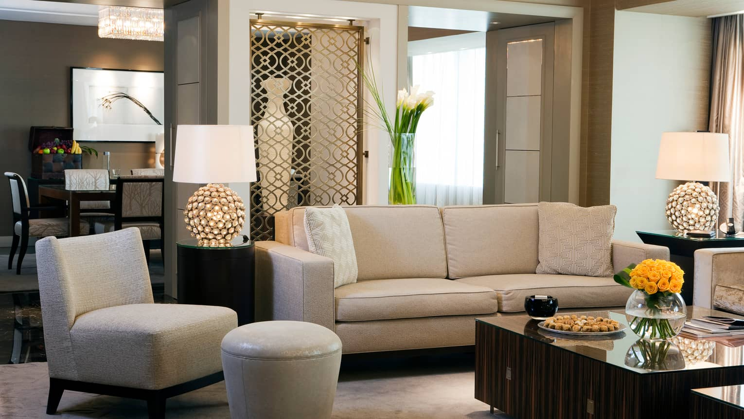 Suite living room with white sofa, chair and ottoman, large wood coffee table, decorative lamp and screen