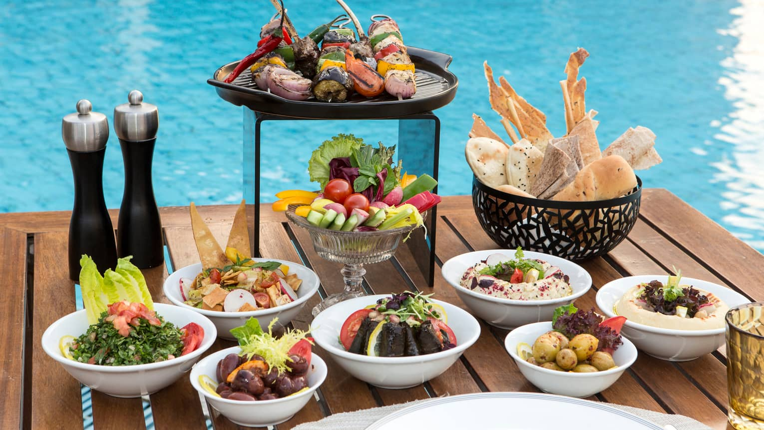 Small bowls of mezze appetizers, like olives, fresh bread, kebabs, on table in front of swimming pool