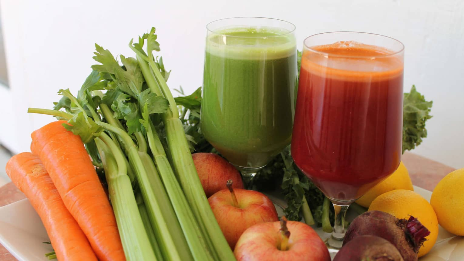 Fresh orange, green juices in glasses next to celery, carrots, apples, beets, lemons