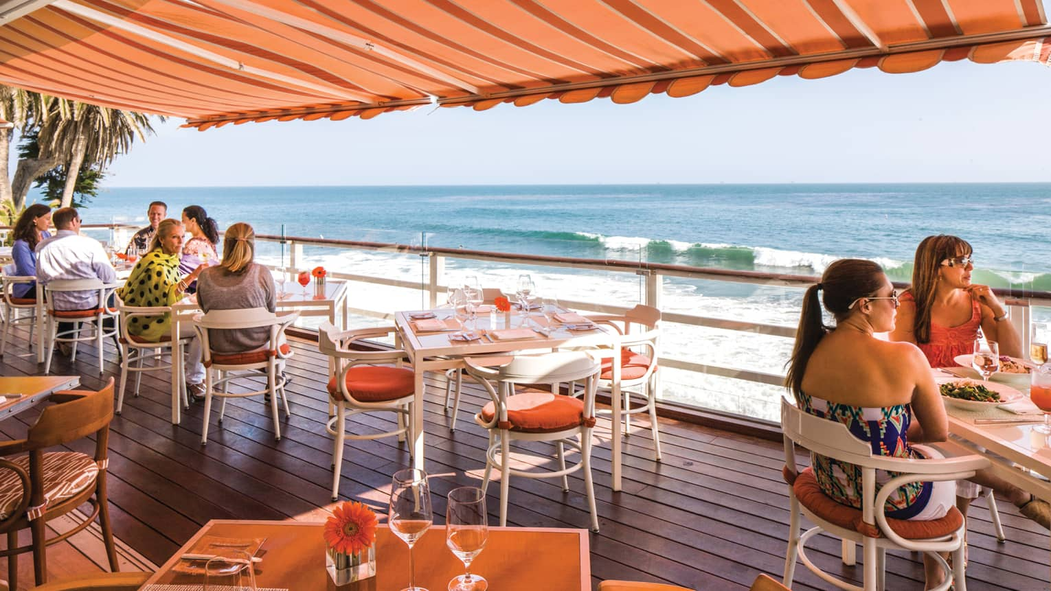 Diners on Tydes restaurant patio under striped orange awning, overlooking beach, ocean