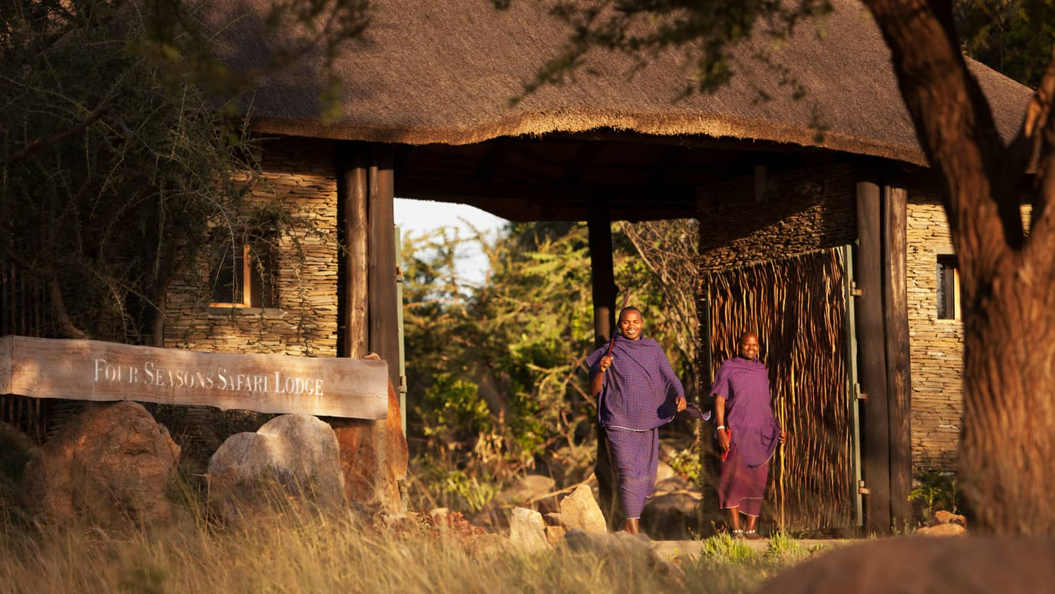 Two people from local Maasai smile, stand by Four Seasons Safari Lodge Serengeti sign