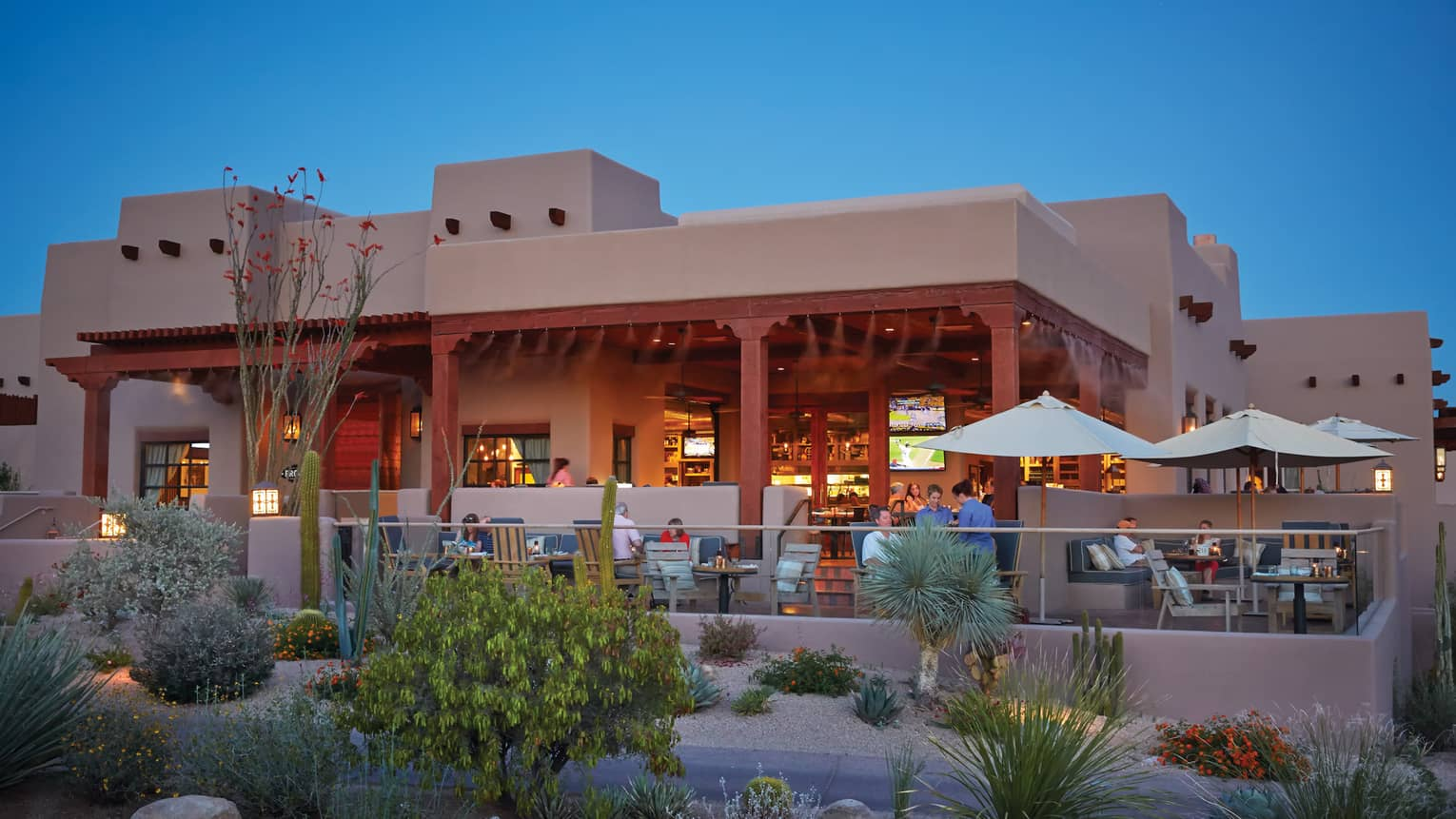 Proof restaurant lounge patio with dining tables, glass balcony, white building exterior, desert shrubs at dusk
