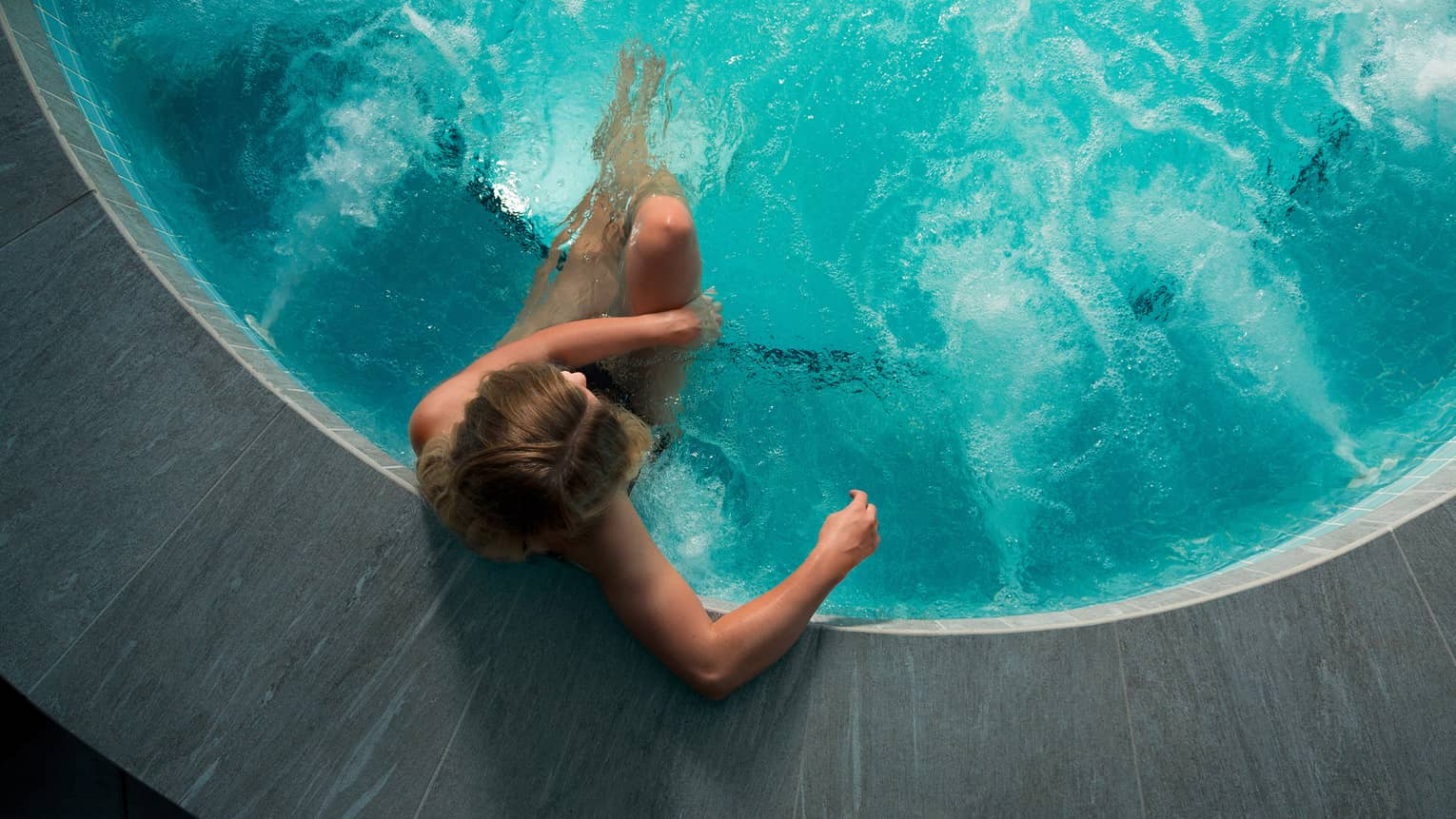 Looking down at woman sitting in round hot tub with blue water