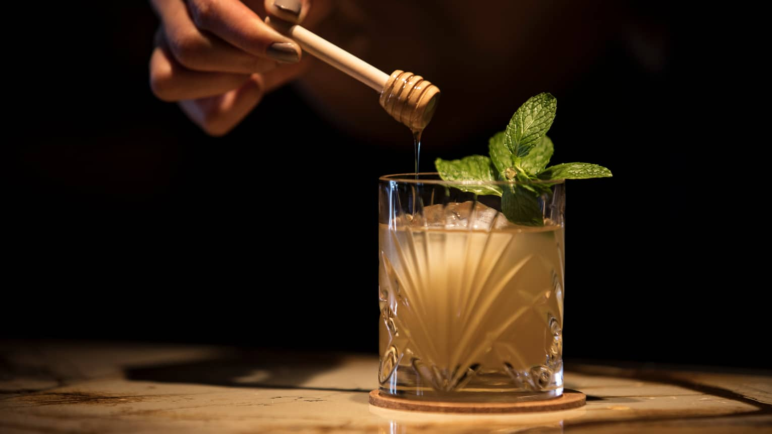 A cocktail with a sprig of mint sits on a table with dim lighting, a hand drizzles honey into it