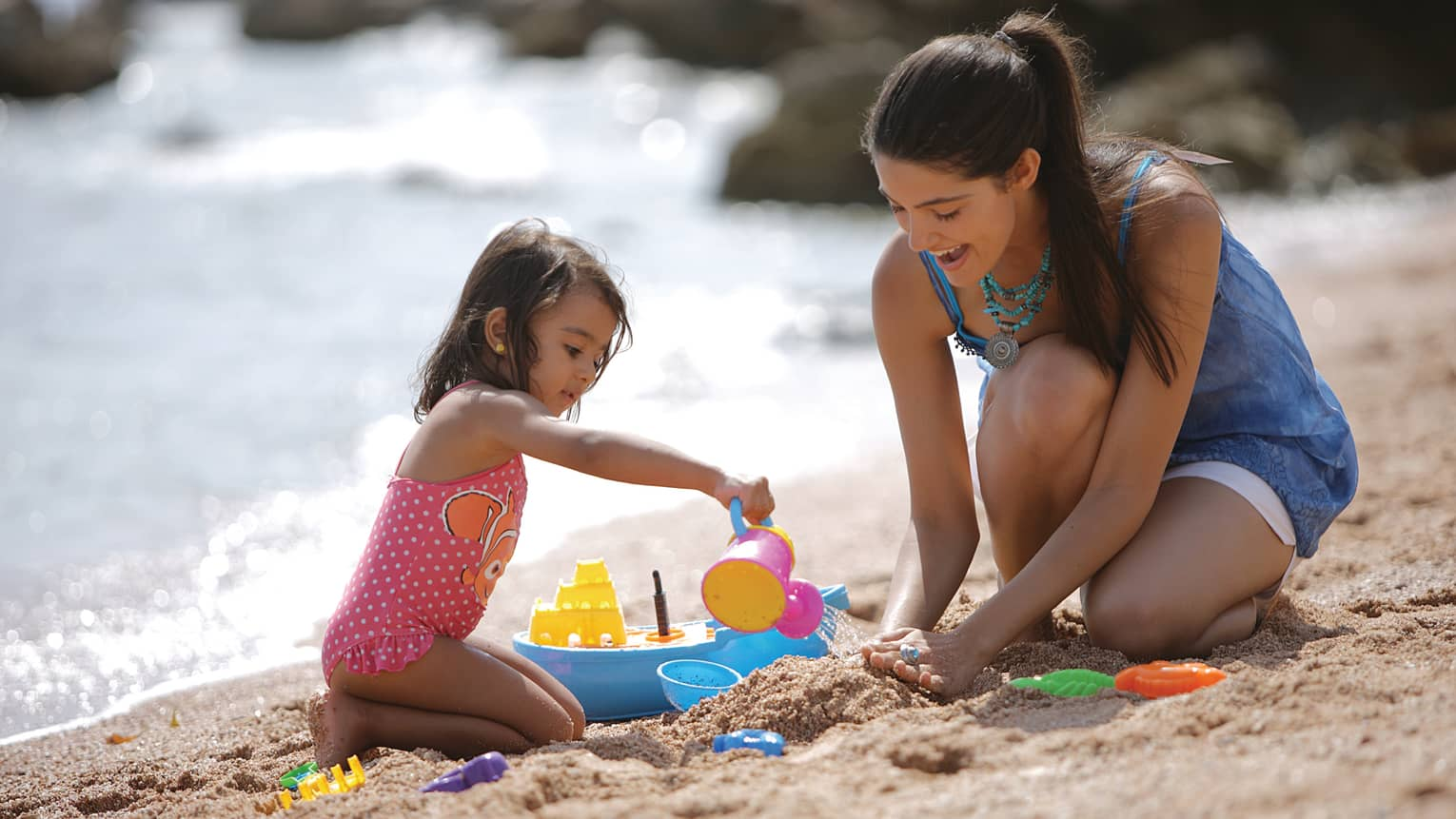 Woman helps young girl build a sandcastle on beach