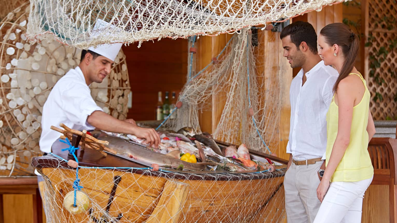 Reef Grill chef in hat displays fresh seafood on ice for couple