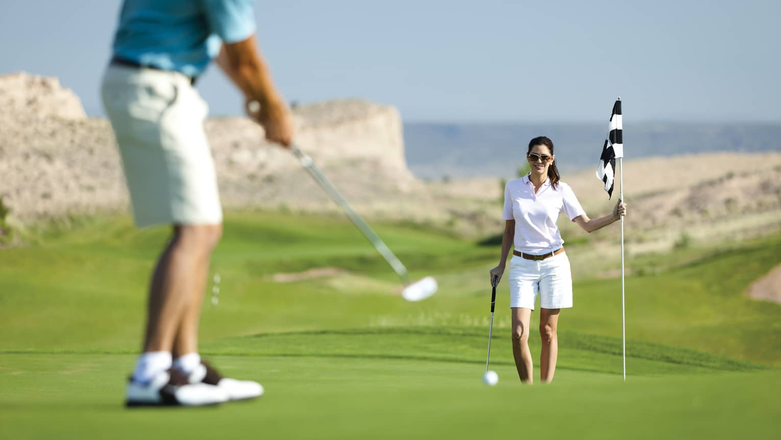 Woman holds golf flag near hole as man putts on course green