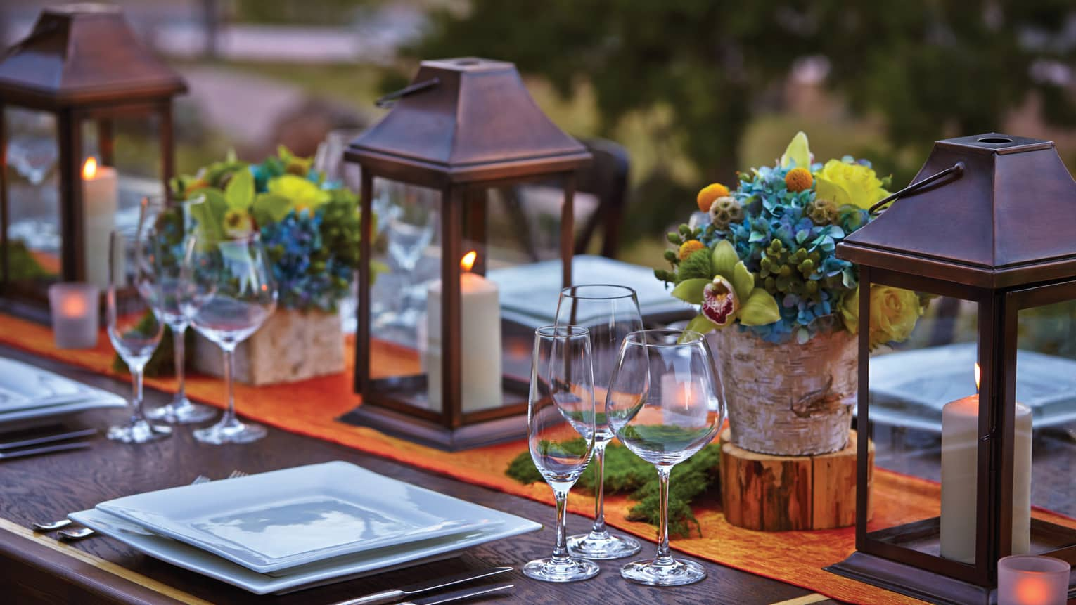 Close-up of lanterns, flowers on patio dining table at sunset